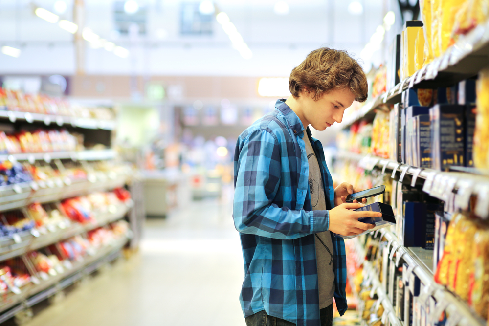 man looking at food label