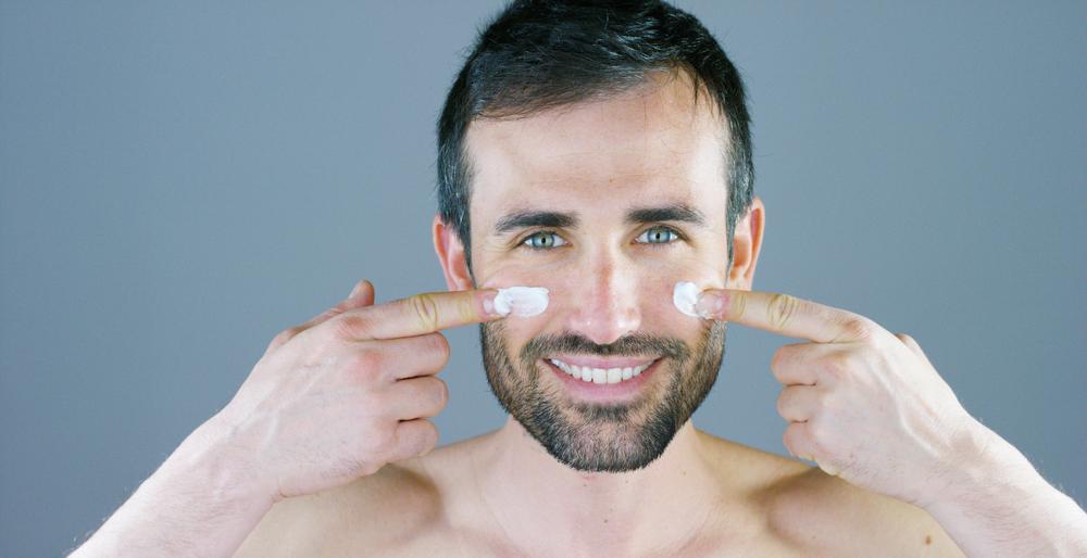 man applying facial cream