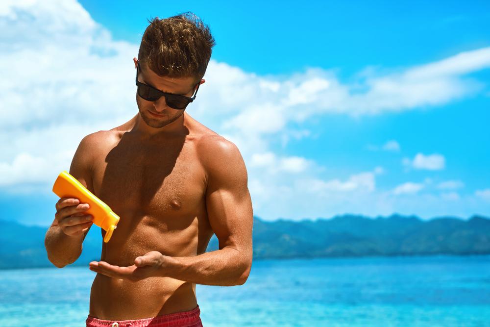 man putting on sunscreen
