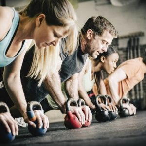 group exercise in gym push up with kettle bell