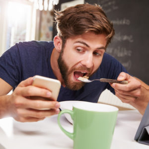 shutterstock_265638692 man distracted by phone while eating