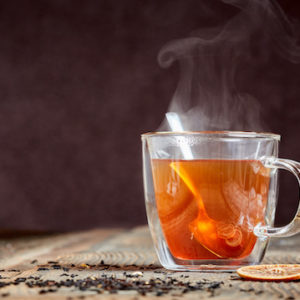 Hot black tea with steam and honey on a wooden table