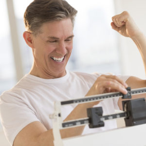 man happy about weight loss seen on scale