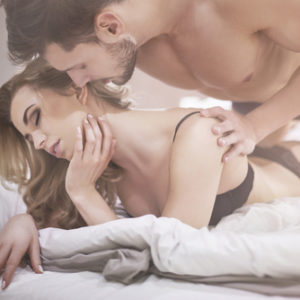 man on top of woman kissing in bed