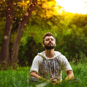 man meditating in forest