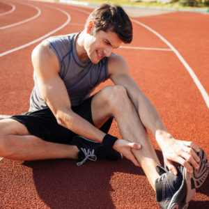 runner suffering from leg cramps on track