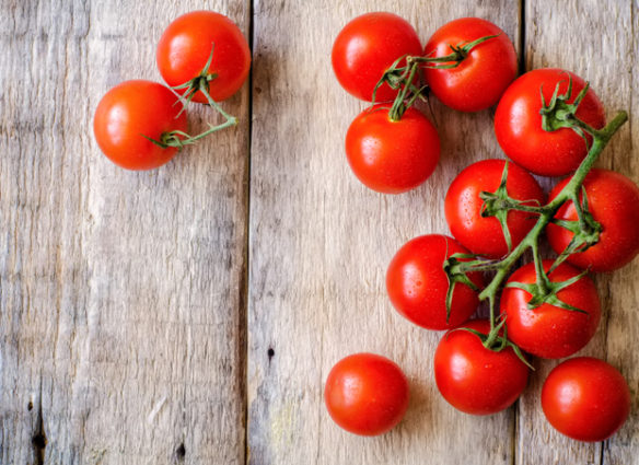 red cherry tomatoes on a white wood background. toning. selective focus on the right tomatoes