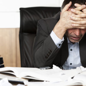 tired businessman with hands on forehead and desk in disarray