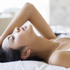 Young woman sleeping on bed looking pleasured