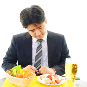 sad man looking at food on table