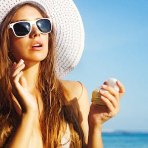 woman in the beach applying sunscreen wearing shades and hat