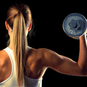 muscular woman lifting dumbbells showing defined arm