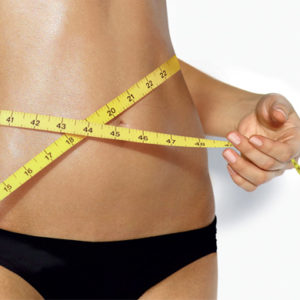 weight loss woman with flat stomach measuring waist
