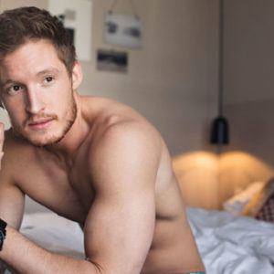 fit young man looking sad sitting on edge of bed
