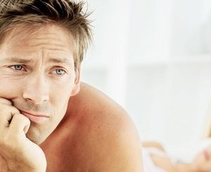 man with erectile dysfunction looking sad in bed