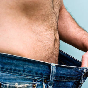 man holding out oversize jeans to show weight loss