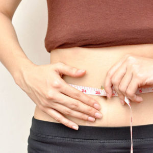 woman taking measurements flat belly