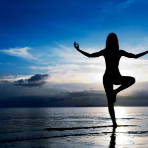 woman doing yoga in beach balancing on one leg
