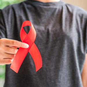 man holding red ribbon for HIV awareness