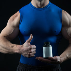 ripped guy wearing tight shirt holding a bottle of supplement