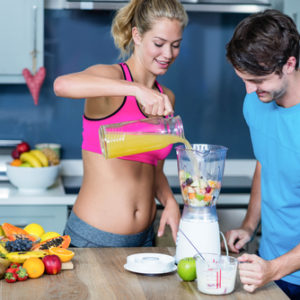 fit couple making fruit smooithie