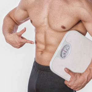 fit guy holding scale pointing at sculpted abs