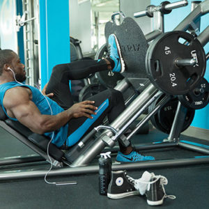 muscular guy doing leg press in gym