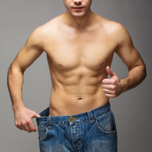 fit guy wearing oversize jeans showing weight loss
