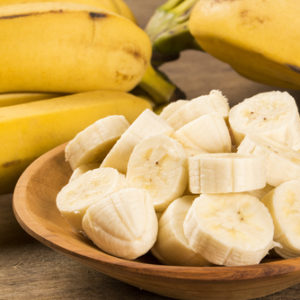 cut up banana slices on wooden bowl