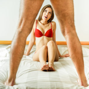 woman licking lips while looking at man's erection