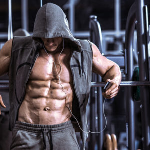 man with ripped abs listening to music in gym
