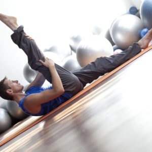 man doing pilates leg stretched