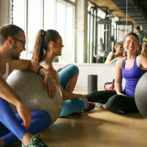 friends chatting in gym studio with stability ball