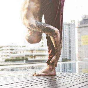 man doing yoga bent over