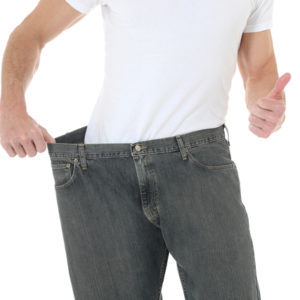 man wearing oversize jeans showing weight loss