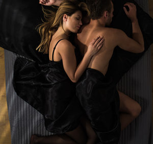 half naked couple asleep in bed black covers