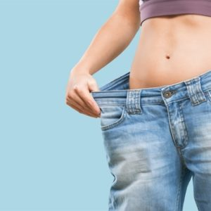 fit woman wearing oversize jeans showing weight loss