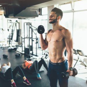 fit man lifting free weights as gym workout