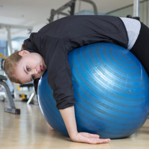 exhausted woman slumped over stability ball