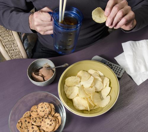 man eating junk food chips and soda