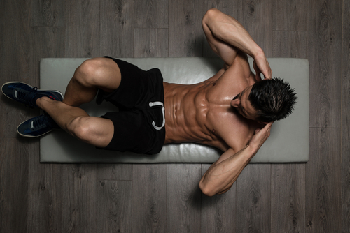 fit guy doing floor crunches and takes Progentra