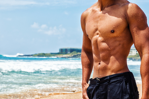 shirtless man with ripped abs who uses Progentra is on the beach