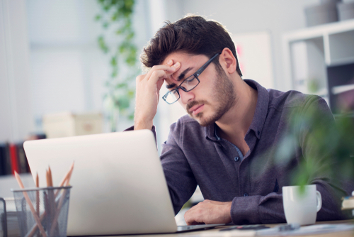 man experiencing headache in office