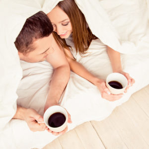 couple drinking coffee under the covers