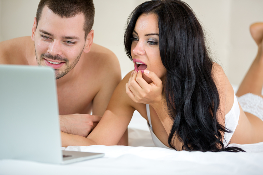 couple in bed watching porn together
