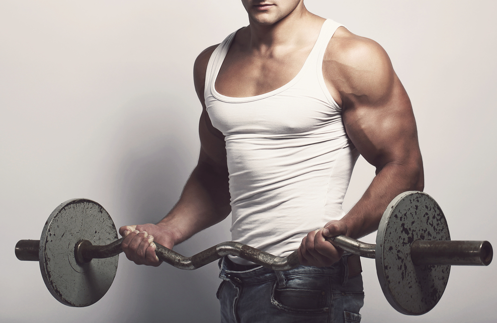 muscular guy with increased testosterone from Progentra lifting weights