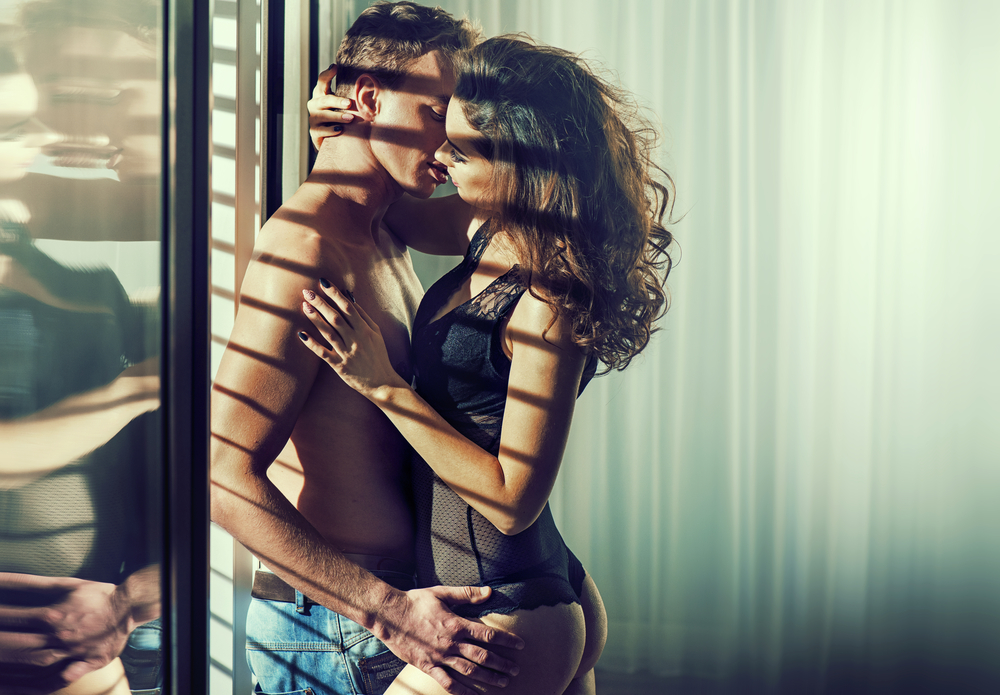 couple kissing by the window after man try out