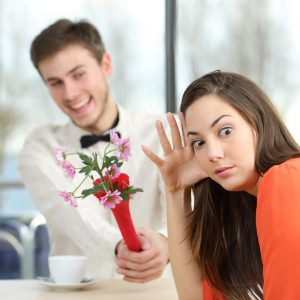man giving flowers to annoyed woman