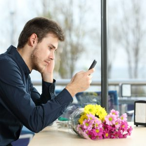 man texting in restaurant stood up by date