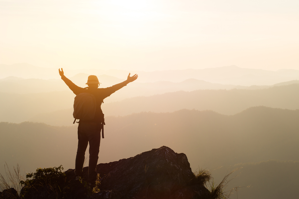 man holding out arms in mountain summit, endorphin high